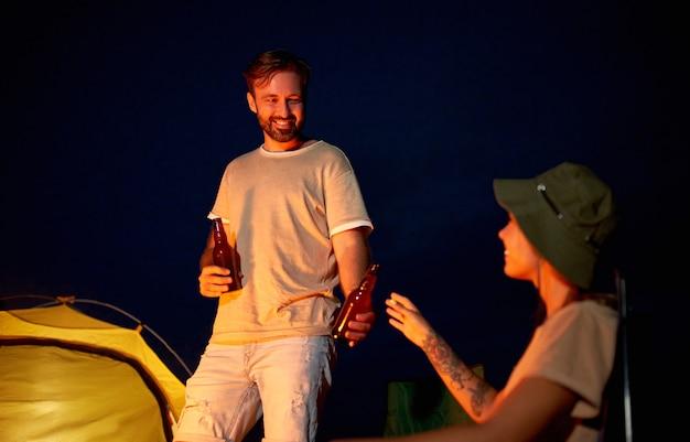 Una donna carina e un bell'uomo sono seduti su sedie pieghevoli vicino alla tenda accanto al fuoco, bevono birra e si divertono di notte sulla spiaggia in riva al mare.