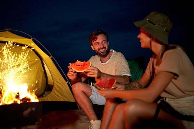 Una donna carina e un bell'uomo sono seduti su sedie pieghevoli vicino alla tenda accanto al fuoco, mangiano anguria e si divertono di notte sulla spiaggia in riva al mare.
