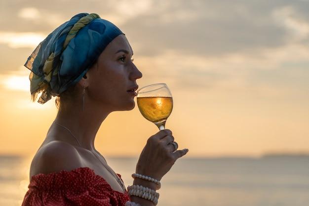 Donna carina che tiene in mano un bicchiere di vino bianco contro un bel tramonto vicino alle onde del mare sulla spiaggia tropicale, primo piano. la ragazza si sta godendo il tramonto con un bicchiere di vino. concetto di svago e viaggio
