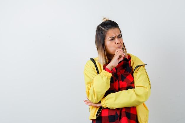 Donna carina che tiene la mano sul mento, distoglie lo sguardo in camicia, giacca e sembra sconvolta, vista frontale.