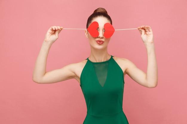 Donna carina che tiene due piccoli cuori rossi che si baciano con gli occhi chiusi