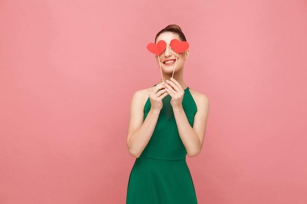 Donna carina che tiene due piccoli cuori rossi chiusi gli occhi sorridenti