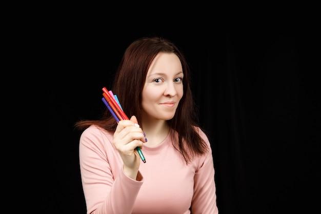La donna carina tiene pennarelli o penne in mano e mostra su uno sfondo nero. copia spazio per il testo.