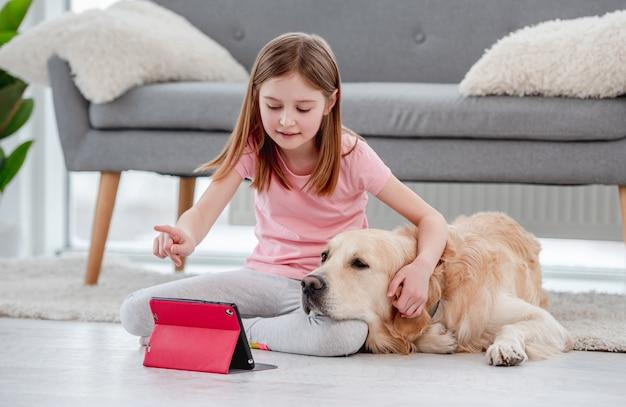 Donna carina che abbraccia il cane golden retriever e parla online con gli amici di famiglia su tablet