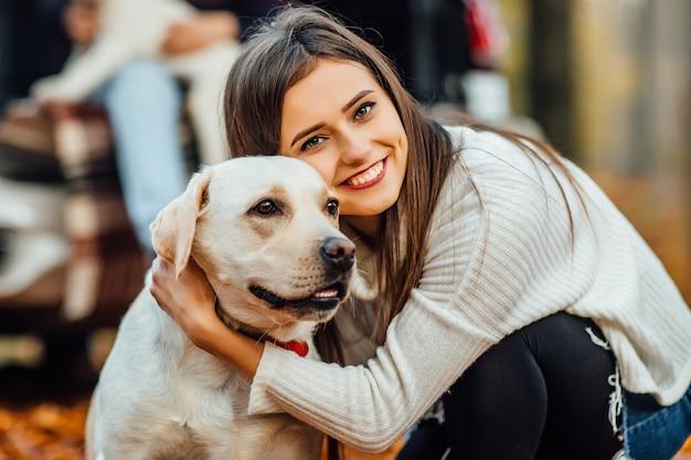 Donna carina che abbraccia il suo labrador golden retriver nel parco.