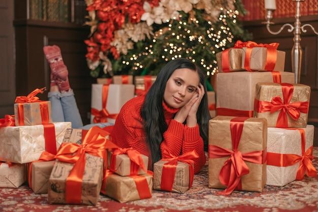 La donna sveglia sta sognando sotto l'albero di natale con i regali che si trovano sul pavimento di legno nella stanza. indossa un maglione lavorato a maglia alla moda, jeans.