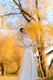 Donna carina in abito da sposa bianco lungo tra alberi autunnali