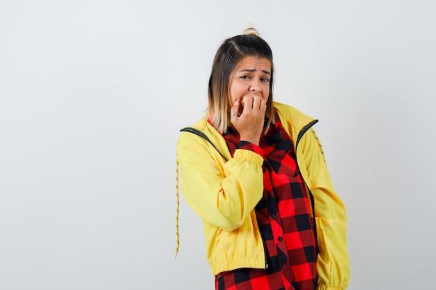 Donna carina in camicia, giacca che si mangia le unghie e sembra ansiosa, vista frontale.