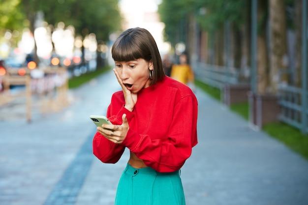 Donna carina in stato di shock guardando nel suo telefono, donna millenaria in maglione rosso elegante con smartphone e scioccato in piedi sulla strada
