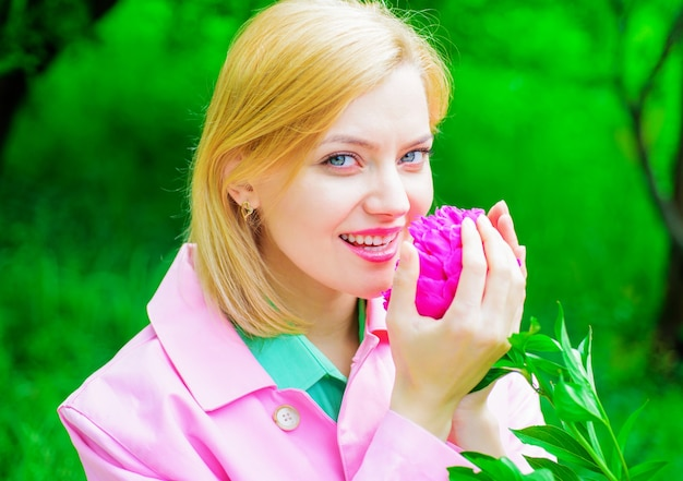 Donna carina che odora di fiori di peonia, bella ragazza con fiore rosa, donna romantica nel parco di primavera