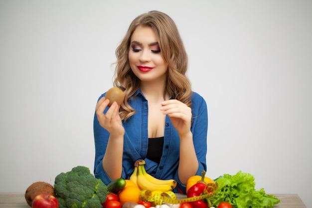 Donna carina a un tavolo in possesso di una mela su uno sfondo di frutta e verdura