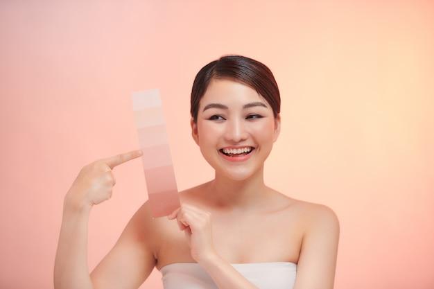 La donna carina prende la scala del colore della pelle sullo sfondo beige