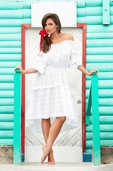 La donna sveglia che porta il bello vestito bianco sta posando vicino alla casa di legno variopinta