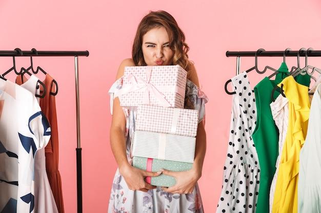 Carino donna che indossa un abito in piedi nel negozio vicino a stendibiancheria con scatole presenti isolato su rosa