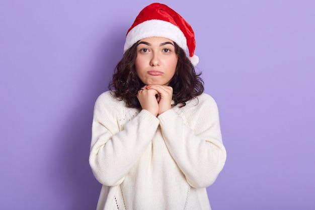 Donna carina con capelli mossi scuri in posa abiti maglione bianco caldo e cappello di babbo natale