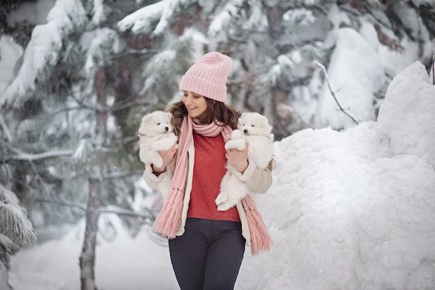 Donna carina con un soffice cucciolo bianco nella foresta invernale