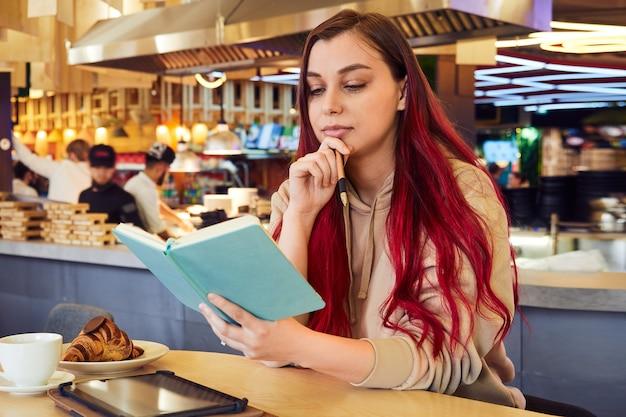 Donna carina con i capelli tinti di rosso lavora a distanza in un bar con un taccuino tra le mani
