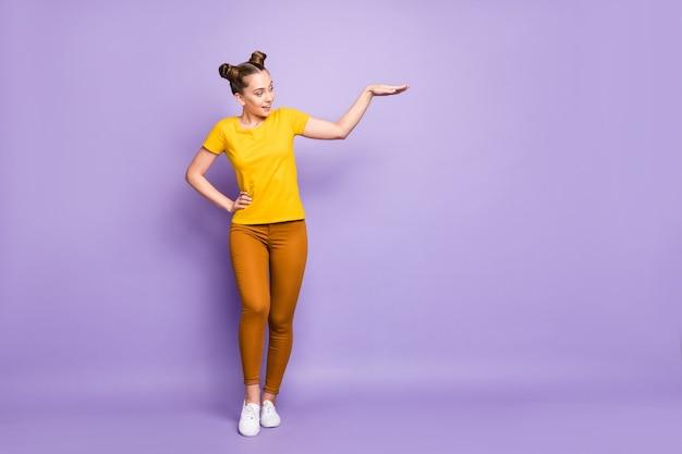 Donna carina con topknots in posa contro il muro viola