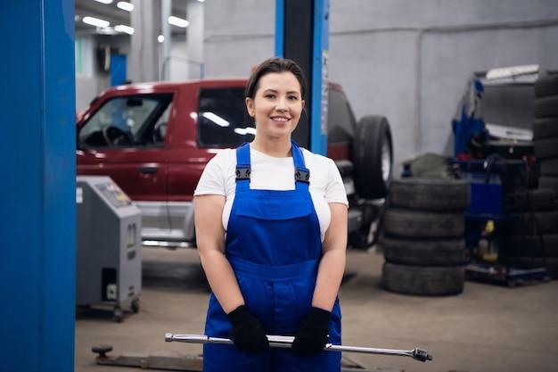 Donna carina in tuta da lavoro tiene una chiave tra le mani e sorride