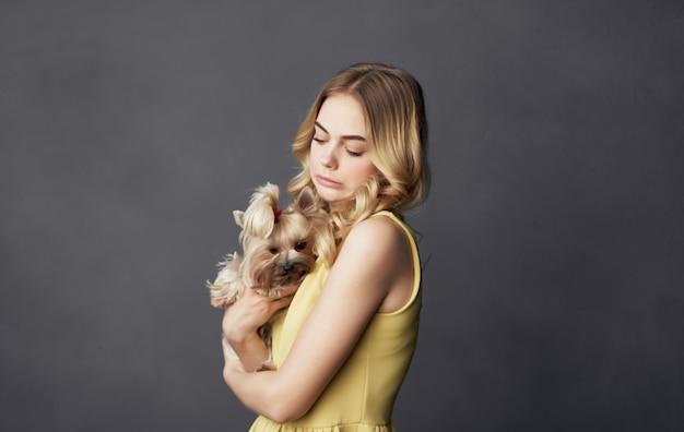 Donna carina in abito giallo con gioia dell'animale domestico di amicizia del piccolo cane di razza.