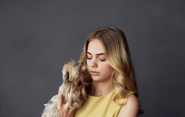 Donna sveglia in vestito giallo con gioia dell'animale domestico di amicizia del piccolo cane di razza