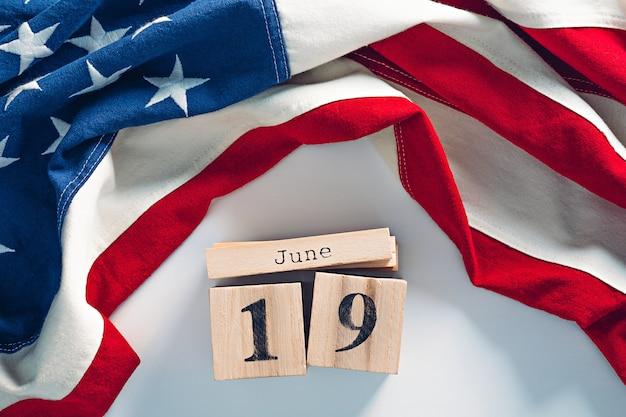 Simpatico calendario a blocchi di legno con data di giugno, 19 e bandiera americana in cotone. juneteenth national independence day concept