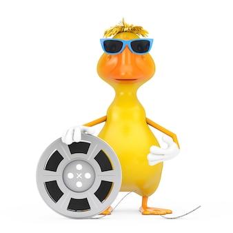Simpatico cartone animato giallo personaggio personaggio mascotte anatra con nastro cinematografico bobina di pellicola su sfondo bianco. rendering 3d