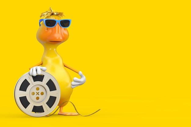 Simpatico cartone animato giallo personaggio personaggio mascotte anatra con nastro cinematografico bobina di pellicola su sfondo giallo. rendering 3d