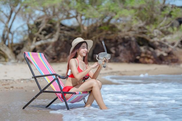 Giovane donna asiatica sveglia in bikini felice sulla bella spiaggia nelle vacanze estive in tailandia