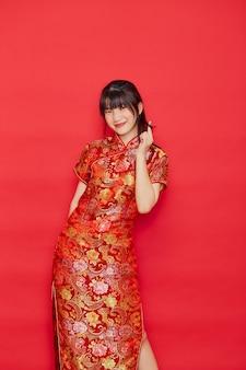 Carina giovane donna asiatica indossare cheongsam con azione per il concetto di capodanno cinese su uno sfondo rosso