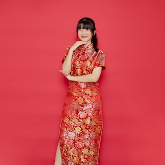 Carina giovane donna asiatica indossare cheongsam con azione per il concetto di capodanno cinese