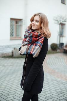 Carina giovane donna attraente in un elegante cappotto invernale caldo in guanti neri con una sciarpa di lana a scacchi vintage alla moda contro un edificio moderno bianco. ragazza meravigliosa che sorride