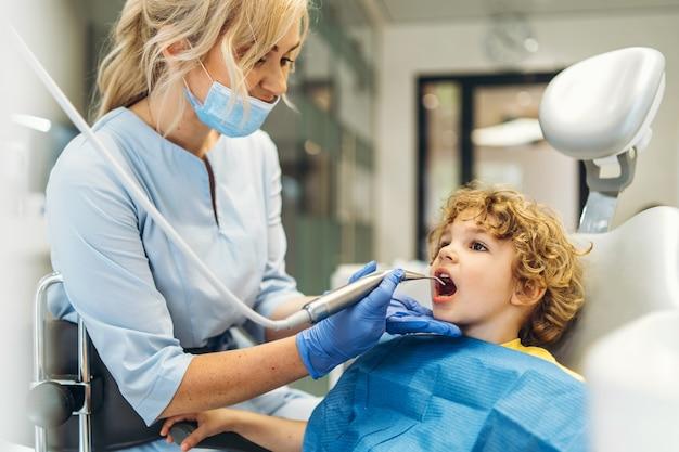 Carino giovane ragazzo in visita dal dentista e avendo i suoi denti controllati dal dentista femminile in studio dentistico
