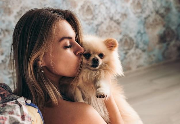 Carina giovane ragazza bruna bacia il suo cane spitz di pomerania. il concetto di comfort domestico e amore e cura degli animali domestici
