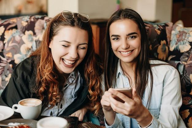 Carina giovane brunetta guardando la telecamera ridendo mentre si tiene uno smartphone mentre la sua ragazza sta ridendo con gli occhi chiusi in un caffè.
