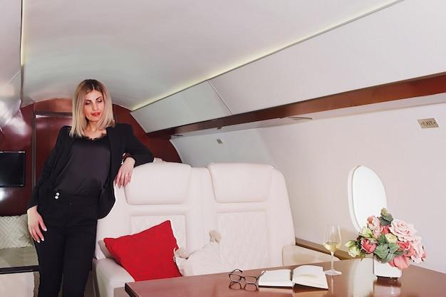Carino giovane imprenditrice che riposa volando in jet privato di lusso. donna d'affari in aereo di prima classe durante il viaggio. concetto di qualità del servizio passeggeri nell'industria aeronautica, viaggiare al massimo