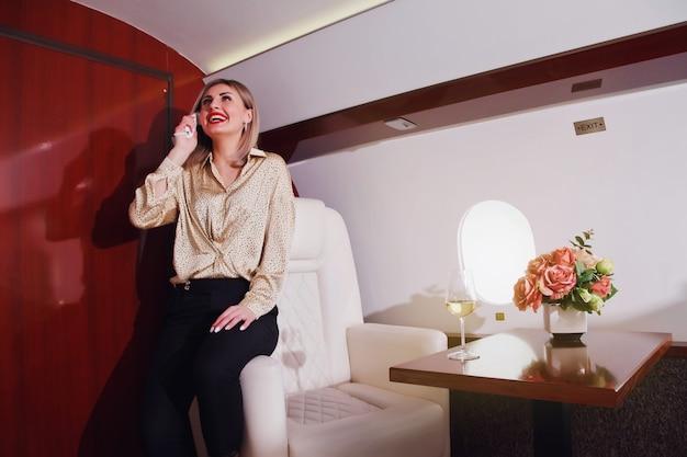 Carino giovane imprenditrice parlando al telefono in volo in jet privato di lusso. donna d'affari in aereo di prima classe durante il viaggio. qualità del concetto di servizio passeggeri nell'industria aeronautica, ai massimi livelli