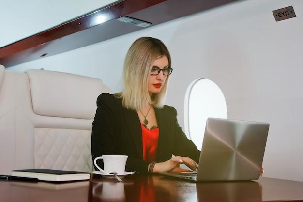 Carina giovane donna d'affari che lavora al computer portatile in jet privato
