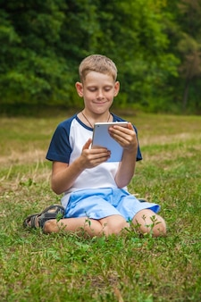 Carino giovane ragazzo caucasico che lavora con il tablet nel parco