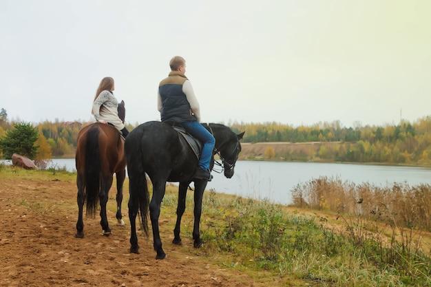 Carino giovane coppia a cavallo nella foresta autunnale in riva al lago. riders in autunno park in tempo nuvoloso inclemente con pioggia leggera. concetto di equitazione all'aperto, sport e tempo libero. copia spazio