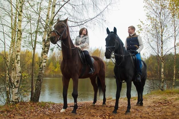 Carino giovane coppia a cavallo nella foresta autunnale in riva al lago. riders in autunno park in tempo nuvoloso inclemente con pioggia leggera