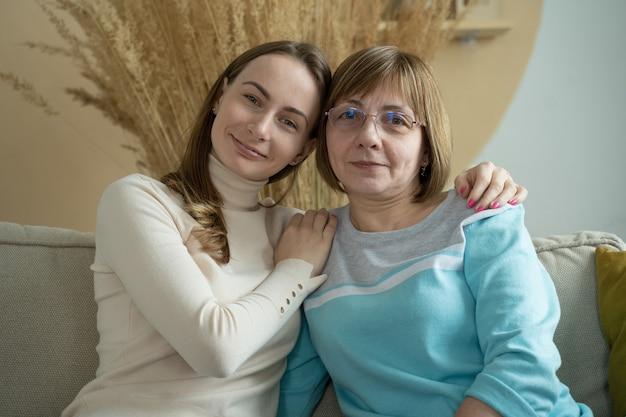 Giovane figlia sveglia in occhiali da vista alla moda hipster che abbraccia sua madre con amore trascorrendo una giornata insieme