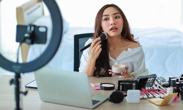 Blogger o vlogger femminile carino e giovane trasmettono o registrano video per blog di bellezza bellezza e cosmetici. l'influencer vive il video sul social network. concetto per blog, videoblog, trucco.