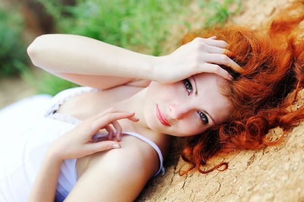 Carina giovane femmina con i capelli rossi che giace a terra