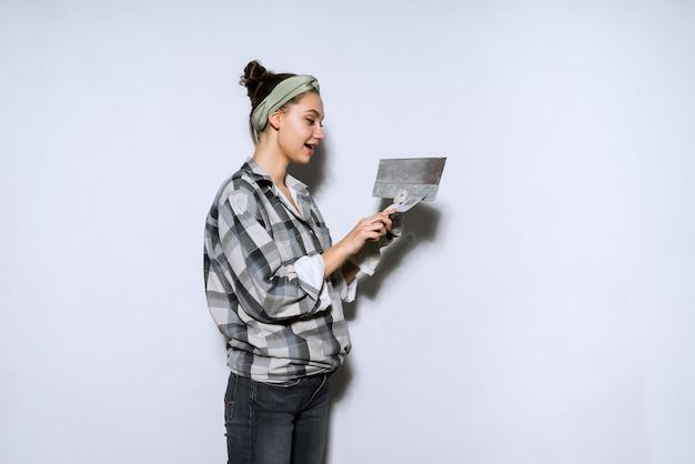 Carina ragazza builder in camicia a quadri che fa riparazioni, livellando le pareti con una spatola