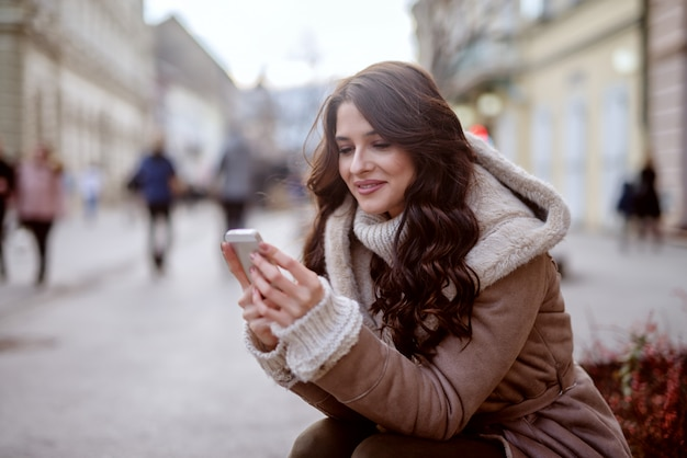 Ragazza carina in cappotto invernale in piedi in strada e guardando il suo telefono. sorridendo e guardando felice.