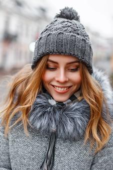 Ragazza carina con un bel sorriso in abiti invernali a maglia in città