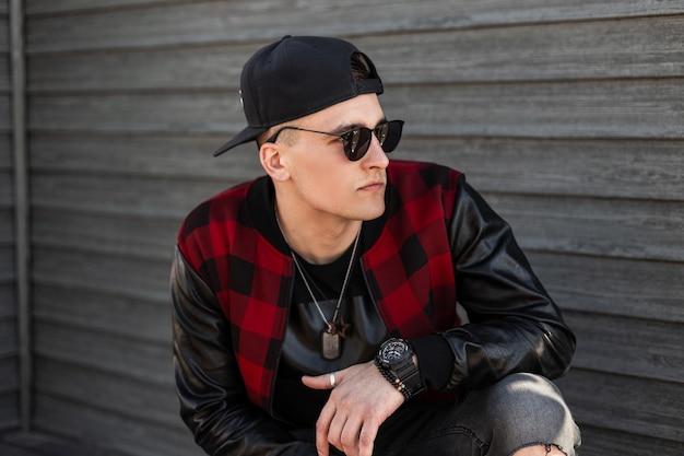 Uomo giovane carino hipster in un berretto da baseball in occhiali da sole neri in una giacca a quadri rossa alla moda in jeans strappati grigi si siede sulla strada vicino a un edificio in legno in un giorno d'estate