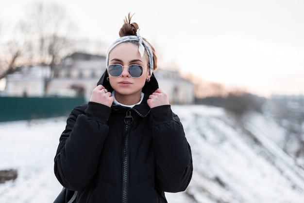 Carina giovane donna hipster in eleganti occhiali da sole neri in giacca invernale alla moda nera con uno zaino in pelle con una bandana cammina in una giornata invernale e godersi il fine settimana