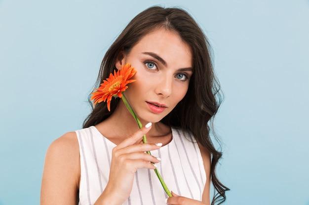 Giovane signora sveglia che posa fiore isolato della tenuta della parete.